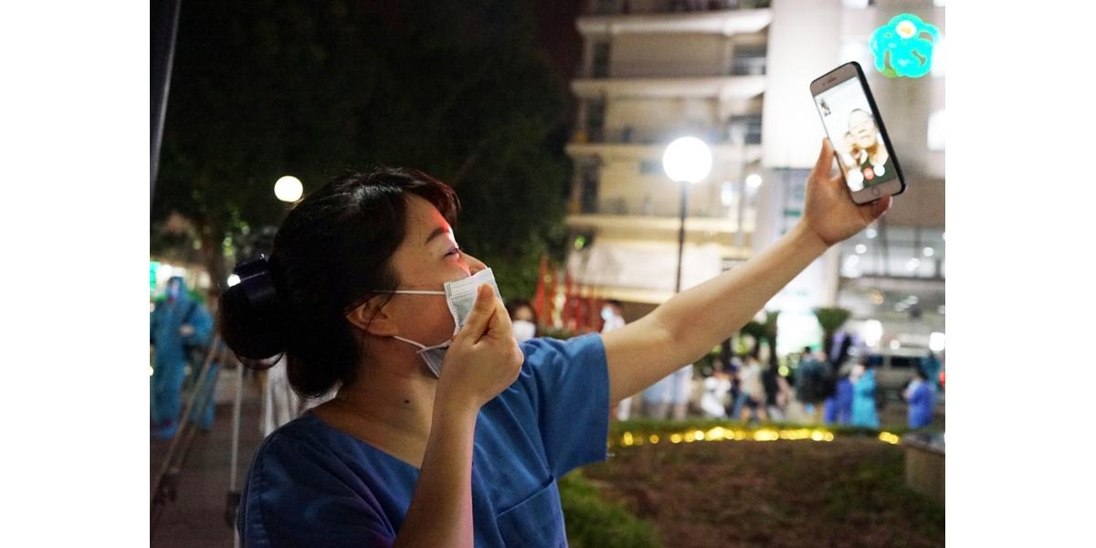 Chị Đặng Hoàng Yến - nhân viên y tế tại Trung tâm Kiểm soát nhiễm khuẩn vui mừng gọi điện cho người thân giữa khuôn viên Bệnh viện Bạch Mai lúc 0h45. Chị vừa khóc nức nở vừa nói bản thân rất nhớ con nên sau khi trời sáng sẽ trở về nhà ôm chặt những thiên