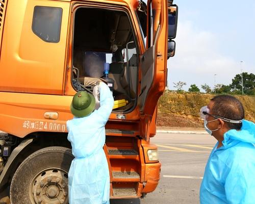 Cán bộ y tế tiến hành phun khử khuẩn buồng lái của xe nhập khẩu qua cầu Bắc Luân 2 - cửa khẩu quốc tế Móng Cái.